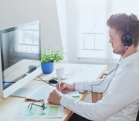 Mann miT Kopfhörern am PC