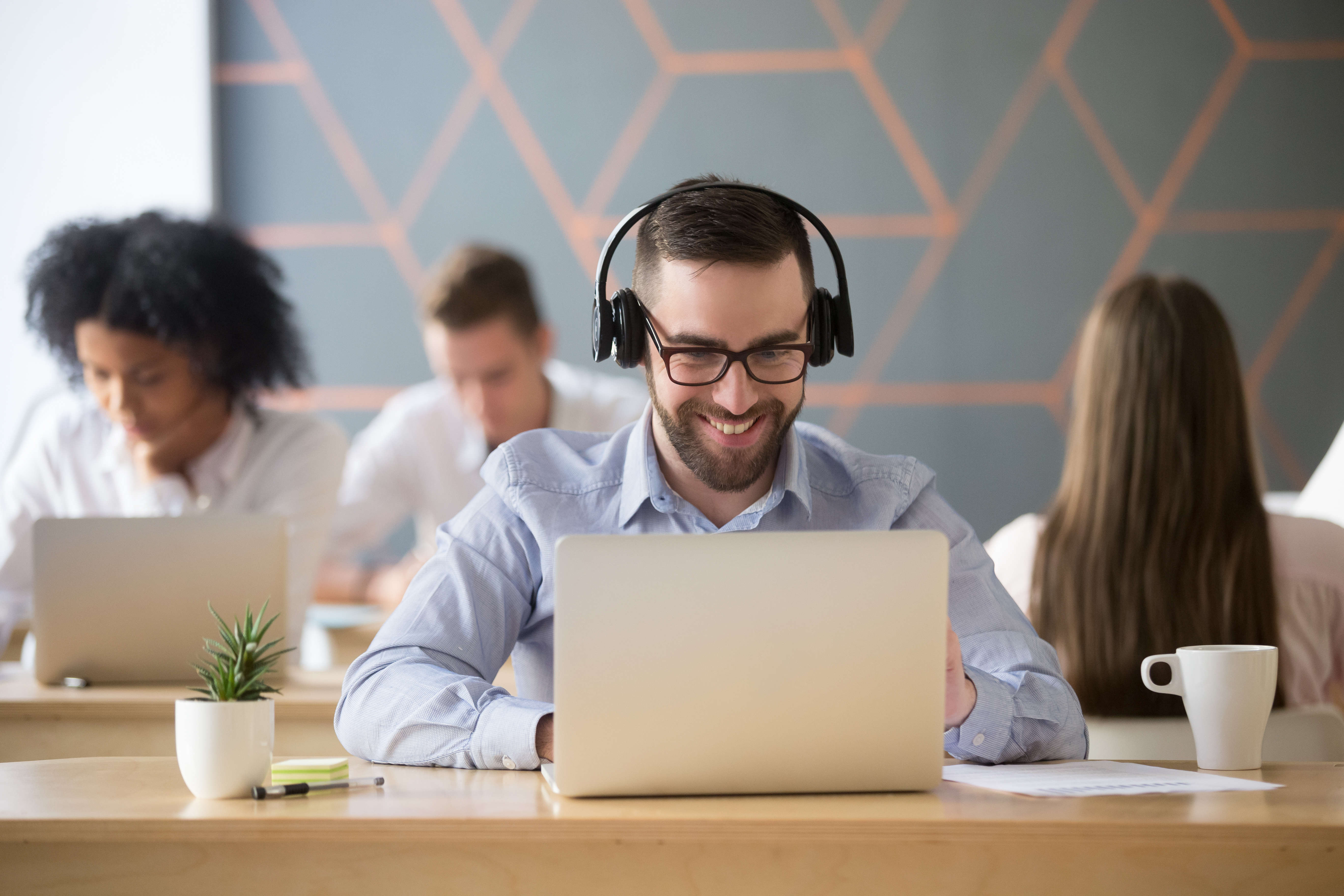 Smiling businessman wearing headphones watching video or consult